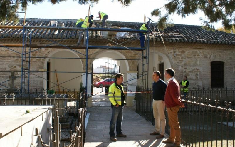 Trabajadores del programa de empleo para menores de 29 años arreglan la cubierta de la entrada al cementerio